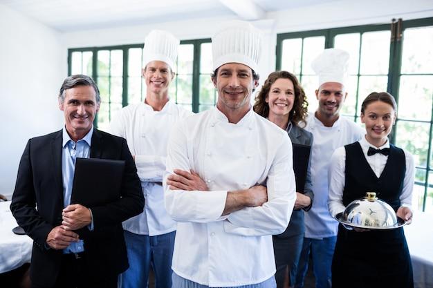 レストランで一緒に立って幸せなレストランチーム