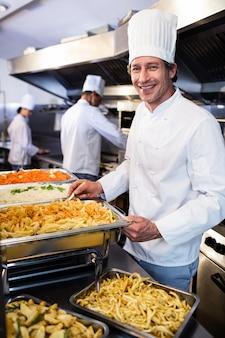 Шеф-повар стоит на подносы с макаронами
