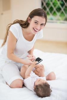 赤ちゃんと遊んでいる間携帯電話を保持している母親を笑顔