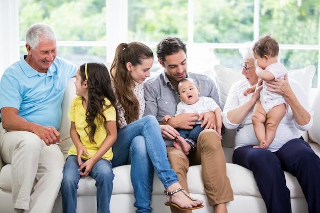 ソファに座っている祖父母と家族の笑顔