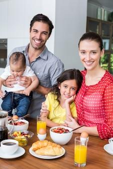 朝食のテーブルで家族の笑顔の肖像画