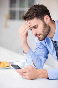 Напряженный бизнесмен с помощью мобильного телефона за столом