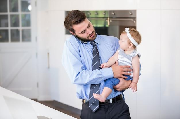 娘を運んでいる間携帯電話で話している実業家