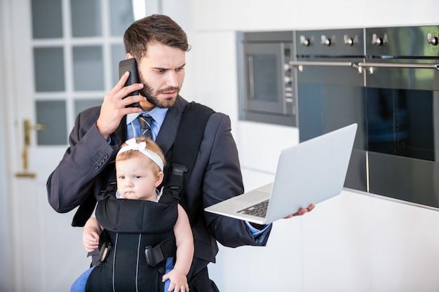 Бизнесмен используя мобильный телефон и компьтер-книжку пока носящ дочь
