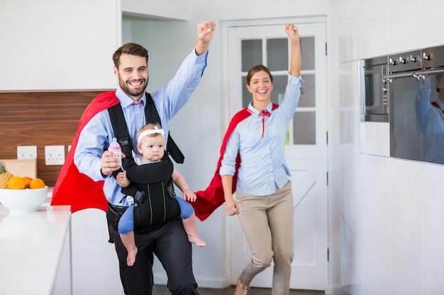 赤ちゃんとスーパーヒーローの衣装で陽気な家族