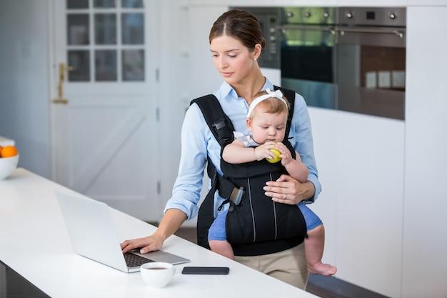 テーブルでノートパソコンを使用しながら女の赤ちゃんを運ぶ女性