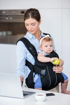 ノートパソコンで作業しながら女の赤ちゃんを運ぶ女性