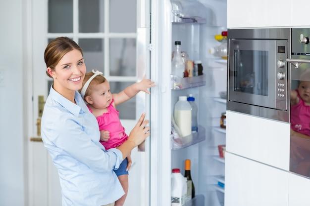 女の赤ちゃんを運んでいる間女性オープニング冷蔵庫