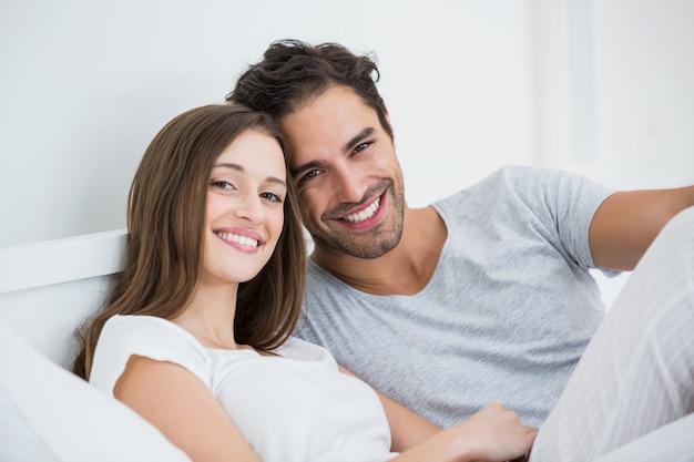 ベッドでリラックスした幸せなカップル