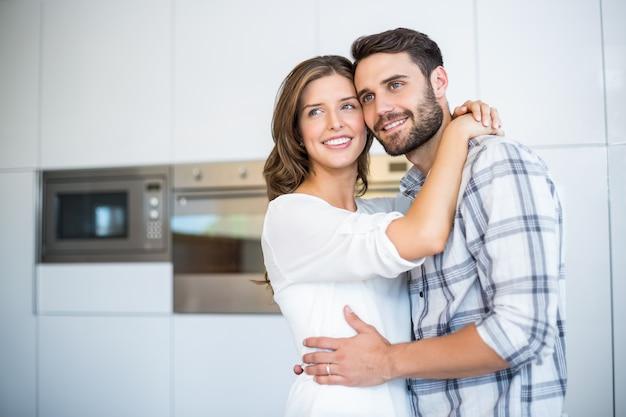 Пара смотрит в сторону, обнимая на кухне
