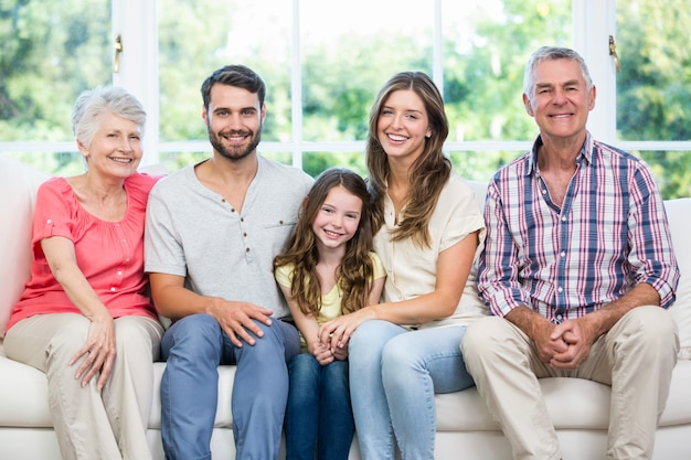 自宅のソファーに座っている幸せな家族