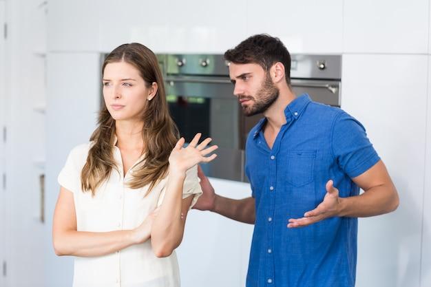 キッチンで妻を混乱させることを説明する男