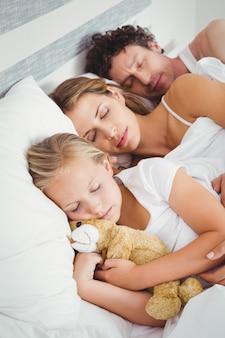 娘と一緒に寝ている両親の高角度のビュー