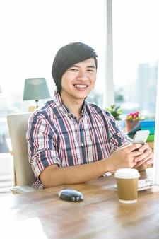 スマートフォンを使用してオフィスで流行に敏感なビジネスマンの笑みを浮かべてください。