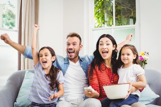 Семья, приветствующая, смотря телевизор дома