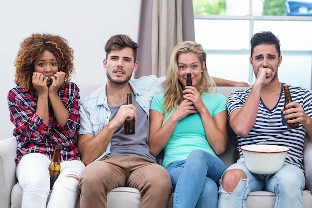 Нервные мульти этнические друзья смотрят телевизор дома
