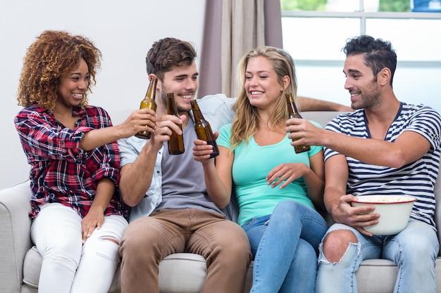 Много этнических друзей тостов пива, сидя на диване