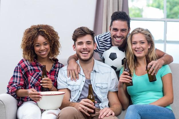 Много этнических друзей, наслаждаясь пивом во время просмотра футбольного матча
