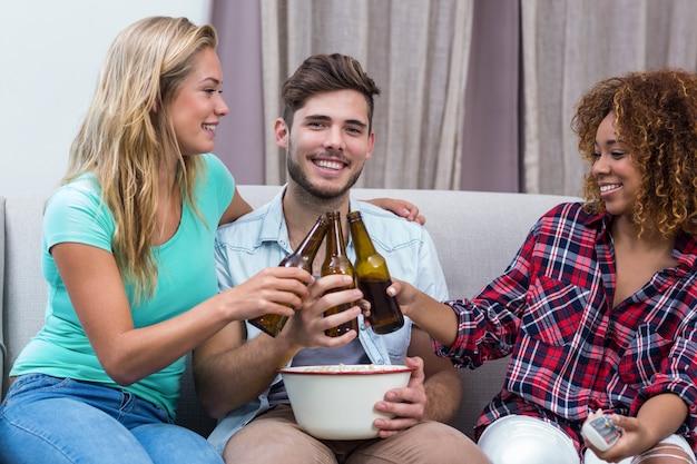 Друзья тостов пива во время просмотра футбольного матча