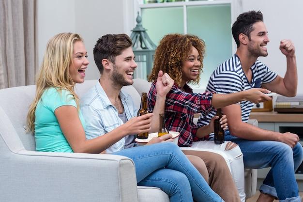 Веселые многоэтнические друзья наслаждаются футбольным матчем дома