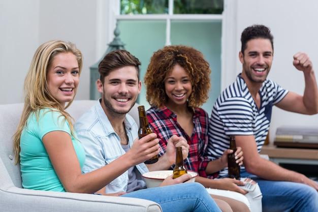 Друзья наслаждаются пивом во время просмотра футбольного матча дома