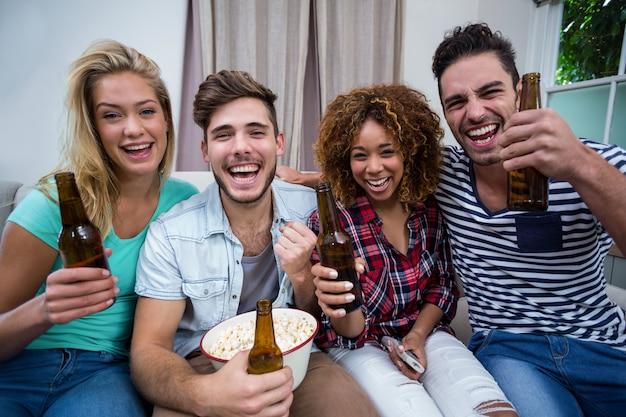 Веселые друзья наслаждаются пивом, наблюдая за матчем дома