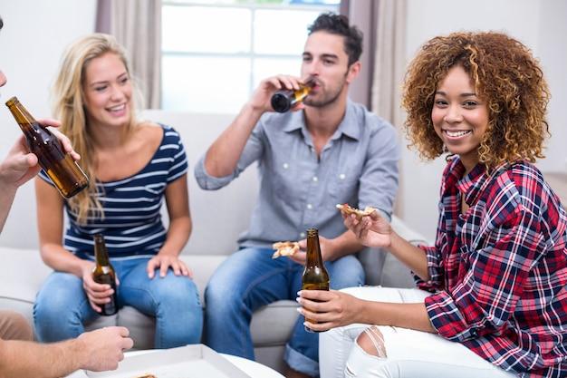 Молодая женщина, наслаждаясь пивом и пиццей с друзьями