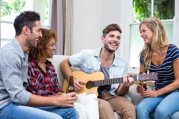 Человек играет на гитаре, а друзья наслаждаются пивом
