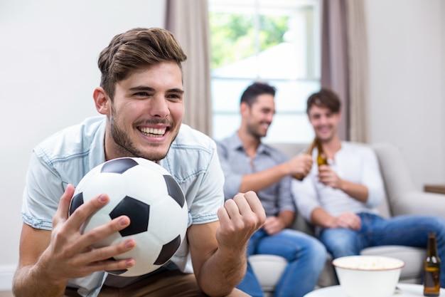 Молодой человек смотрит футбольный матч в то время как друзья