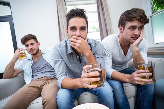 Расстроенные друзья-мужчины пьют алкоголь во время просмотра телевизора