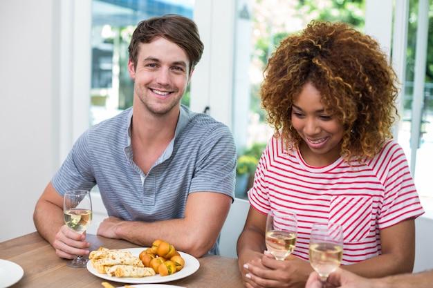 Юные друзья с вином и едой на столе