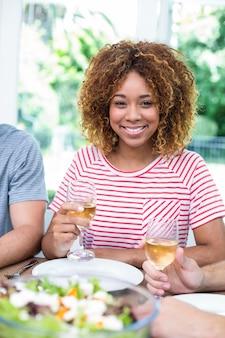 Счастливая молодая женщина пьет вино с друзьями