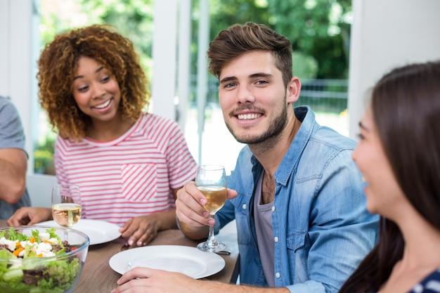 Молодой человек пьет вино с друзьями дома