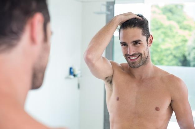 鏡を見ながら笑っている上半身裸の若い男