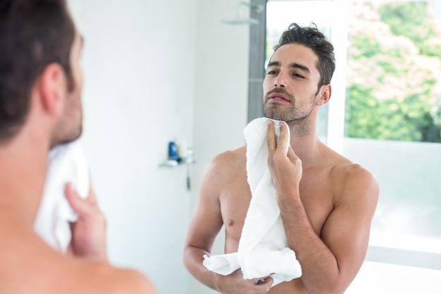 若い男が鏡を見ながら顔を拭く