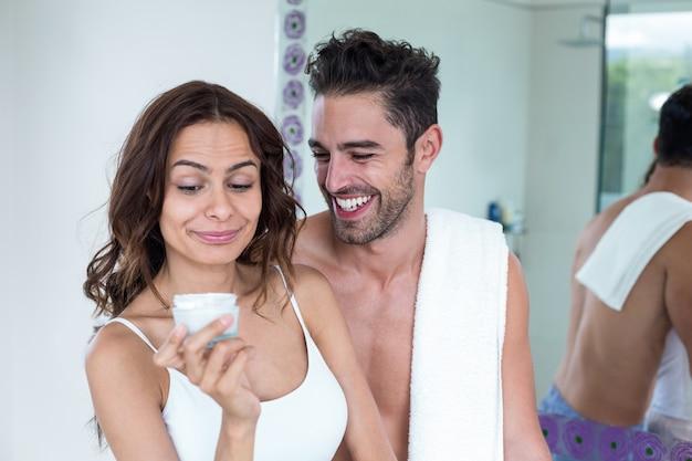 夫が彼女のそばに笑みを浮かべながらクリームを見て女性