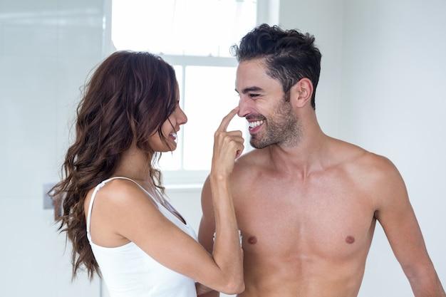 夫の顔にクリームを塗る妻