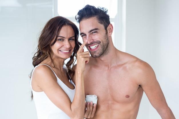 家で夫の顔にクリームを塗る妻