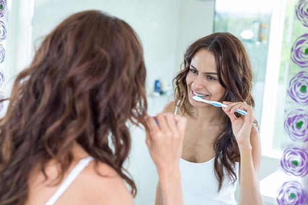 鏡を見ながら歯を磨く女性