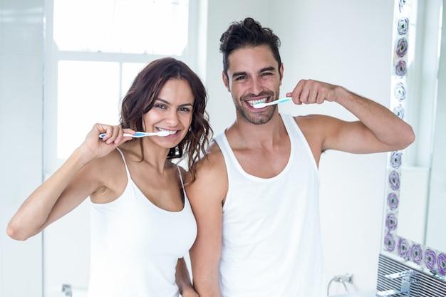 Молодая пара чистит зубы в ванной комнате