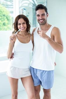 Молодая пара счастлива чистить зубы, стоя в ванной комнате