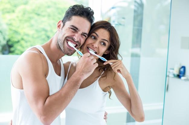 若いカップルが浴室に立っている間歯を磨く