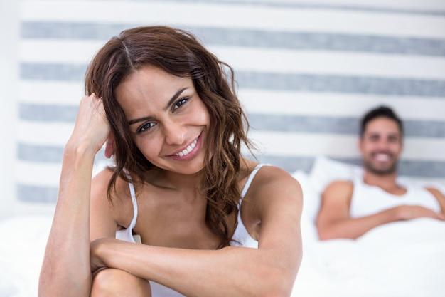 夫がベッドに横たわっている間笑顔の女性