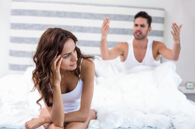 夫が彼女に叫びながら座っている女性