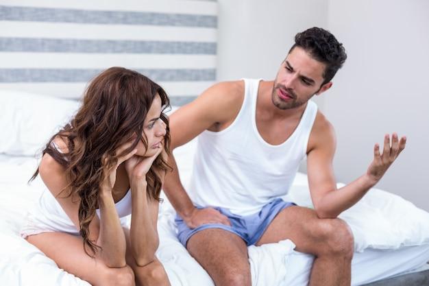 若いカップルがベッドの上に座っていると主張