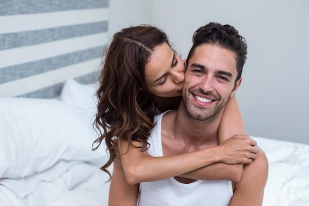 妻にキスをし、ベッドの上の夫を抱きしめる