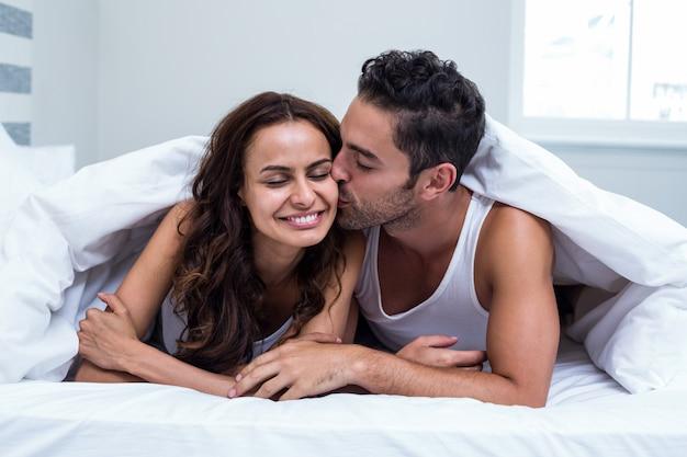 毛布の下に横たわっている間笑みを浮かべて男キス女性