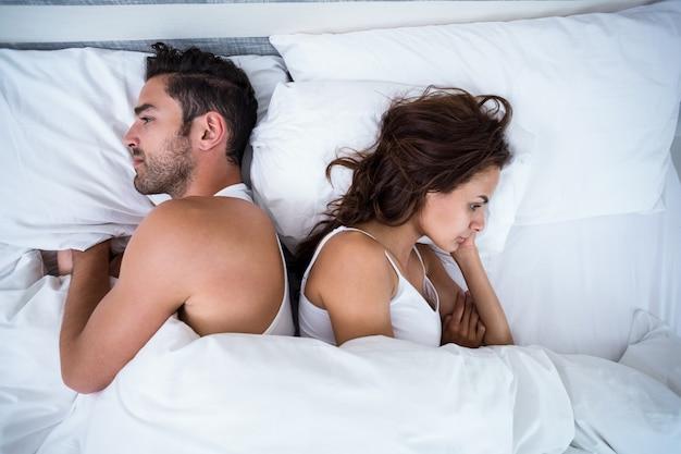 ベッドの上の怒っているカップルの高角度のビュー