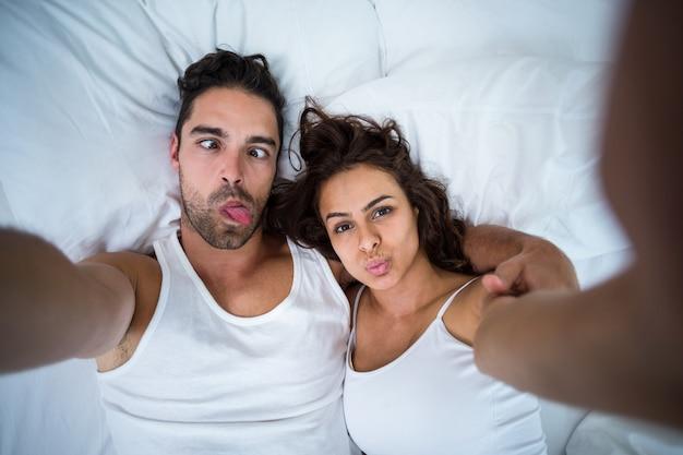 セルフポートレートを撮影しながら顔を作るカップル