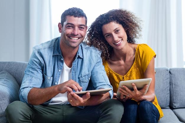 肖像若いカップルのソファーに座っているとデジタルタブレットを使用して